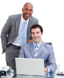 Smiling manager assisting his colleague Stock Photo