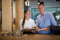 Smiling manager and bartender standing at bar counter Royalty Free Stock Images