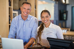 Smiling manager and bartender standing at bar counter Royalty Free Stock Photos