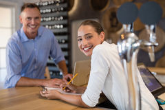 Smiling manager and bartender standing at bar counter. Portrait of smiling manager and bartender standing at bar counter royalty free stock photo