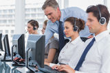 Smiling manager helping call centre agent. With a headset Royalty Free Stock Photo