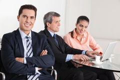 Smiling manager with his arms. Crossed sitting in the office with team in background Stock Photography