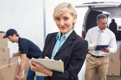 Smiling manager holding clipboard in front of his colleagues Royalty Free Stock Photography