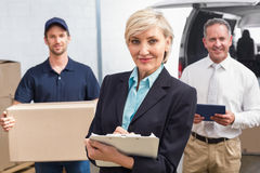 Smiling manager holding clipboard in front of his colleagues Royalty Free Stock Photos