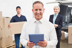 Smiling manager holding tablet in front of his colleagues Royalty Free Stock Image