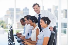 Smiling manager looking at camera. While call centre employees working on computers Royalty Free Stock Image