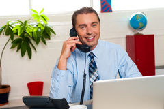 Smiling manager in middle of business interactions Royalty Free Stock Photo