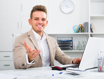 Smiling manager at office desk with laptop Stock Photo