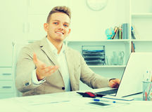 Smiling manager at office desk with laptop Stock Images