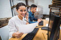 Smiling manager on the phone holding a document Stock Photos
