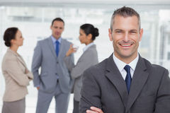 Smiling manager posing with employees in background royalty free stock photo