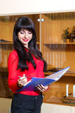 Smiling manager in red blouse with a folder of documents in th Royalty Free Stock Images