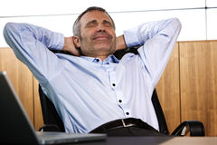 Smiling manager relaxing in office chair. Royalty Free Stock Image