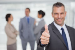 Smiling manager showing thumb up with employees in background Stock Photos