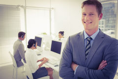 Smiling manager standing arms crossed with staff behind Royalty Free Stock Image