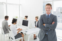 Smiling manager standing arms crossed with staff behind Stock Photography