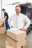 Smiling manager standing behind stack of cardboard boxes Stock Photos