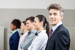 Smiling Manager Standing In Row With Team Royalty Free Stock Images