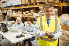 Smiling manager wearing yellow vest using handheld Stock Photos