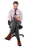 Smiling manager working on tablet device Royalty Free Stock Photography