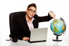 Smiling manageress pointing to a globe Royalty Free Stock Image