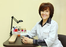Smiling manicurist sits at table for manicure Royalty Free Stock Images
