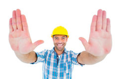 Smiling manual worker gesturing stop sign. Portrait of smiling manual worker gesturing stop sign on white background Royalty Free Stock Image