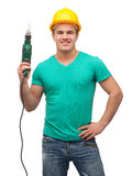 Smiling manual worker in helmet with drill machine Stock Photography
