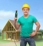 Smiling manual worker in helmet with drill machine Royalty Free Stock Image