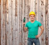 Smiling manual worker in helmet with drill machine Royalty Free Stock Photography