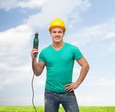 Smiling manual worker in helmet with drill machine Stock Image