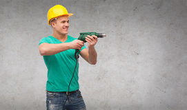 Smiling manual worker in helmet with drill machine. Repair, construction and maintenance concept - smiling male manual worker in protective helmet with drill royalty free stock photos