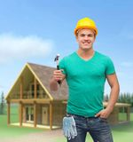 Smiling manual worker in helmet with hammer Royalty Free Stock Images