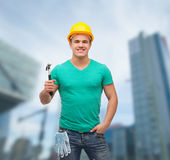 Smiling manual worker in helmet with hammer Stock Photo