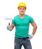 Smiling manual worker in helmet with paint roller Royalty Free Stock Images