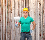 Smiling manual worker in helmet with paint roller. Repair, construction and maintenance concept - smiling male manual worker in protective helmet with paint Royalty Free Stock Image