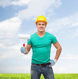 Smiling manual worker in helmet with paint roller Stock Images