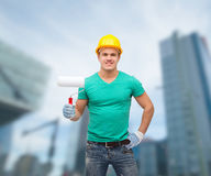 Smiling manual worker in helmet with paint roller Stock Photos