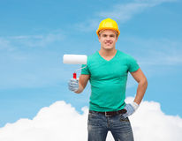 Smiling manual worker in helmet with paint roller Stock Photo