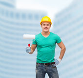 Smiling manual worker in helmet with paint roller Royalty Free Stock Photos