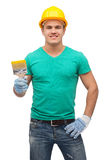 Smiling manual worker in helmet with paintbrush Stock Images