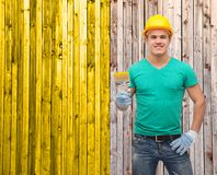 Smiling manual worker in helmet with paintbrush Stock Image