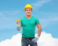 Smiling manual worker in helmet with paintbrush Stock Photo