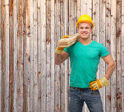 Smiling manual worker in helmet with wooden boards. Repair, construction and maintenance concept - smiling male manual worker in protective helmet carrying Royalty Free Stock Image