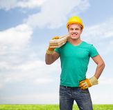 Smiling manual worker in helmet with wooden boards Stock Image