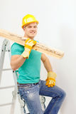 Smiling manual worker in helmet with wooden boards. Repair, construction and maintenance concept - smiling male manual worker in protective helmet carrying Stock Photography