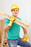 Smiling manual worker in helmet with wooden boards. Repair, construction and maintenance concept - smiling male manual worker in protective helmet carrying Stock Photos