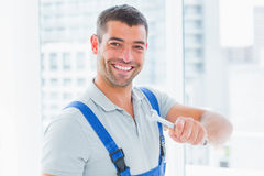 Smiling manual worker holding spanner in office Royalty Free Stock Images