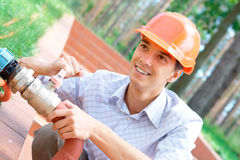 Smiling manual worker repairing pipe. Photo of a smiling manual worker repairing a pipe outdoors royalty free stock image