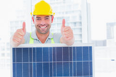 Smiling manual worker with solar panel gesturing thumbs up. Portrait of smiling manual worker with solar panel gesturing thumbs up in bright office stock photography